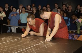 A crowd watches as two monks stand close over the table to continue drawing guidelines. The dark table is covered in a complex grid.