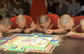 Several monks in red lean against the table to work on the mandala, while another monk faces and engages with a crowd behind them.