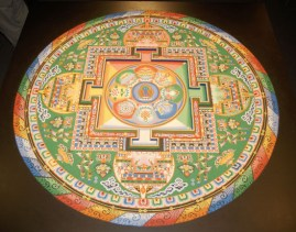 The completed mandala - intricate and colorful - in bright red, yellow, green, blue, and white.