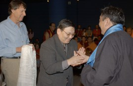 Two men shake hands, while a third man holding a white cloth stands to the side.
