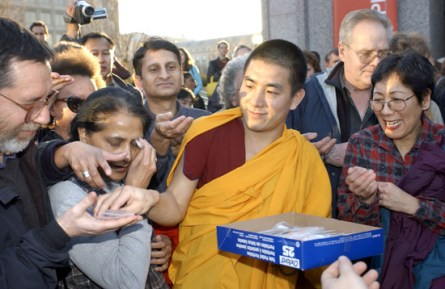 A smiling young monk distributes small bags of sand from the destroyed mandala to people outside the museum.
