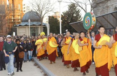 A procession of monks walking past the Freer.