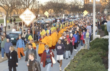 A procession of monks along with a crowd of people walking from the museum in the direction of the Tidal Basin.