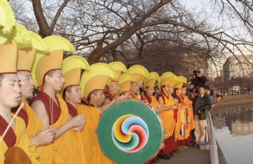 Monks in red and gold robes, wearing yellow crested head-dresses line up around the Tidal Basin. One of them holds a colorful gankyil.