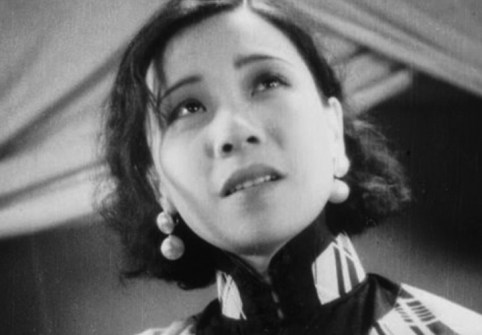 Close up of Ruan Lingyu in black and white silent film The Goddess, she wears a high neck collar and dangling earrings