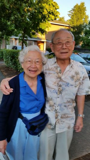 An elderly couple standing close together, the man is taller and has his arm around the shoulder of the woman.