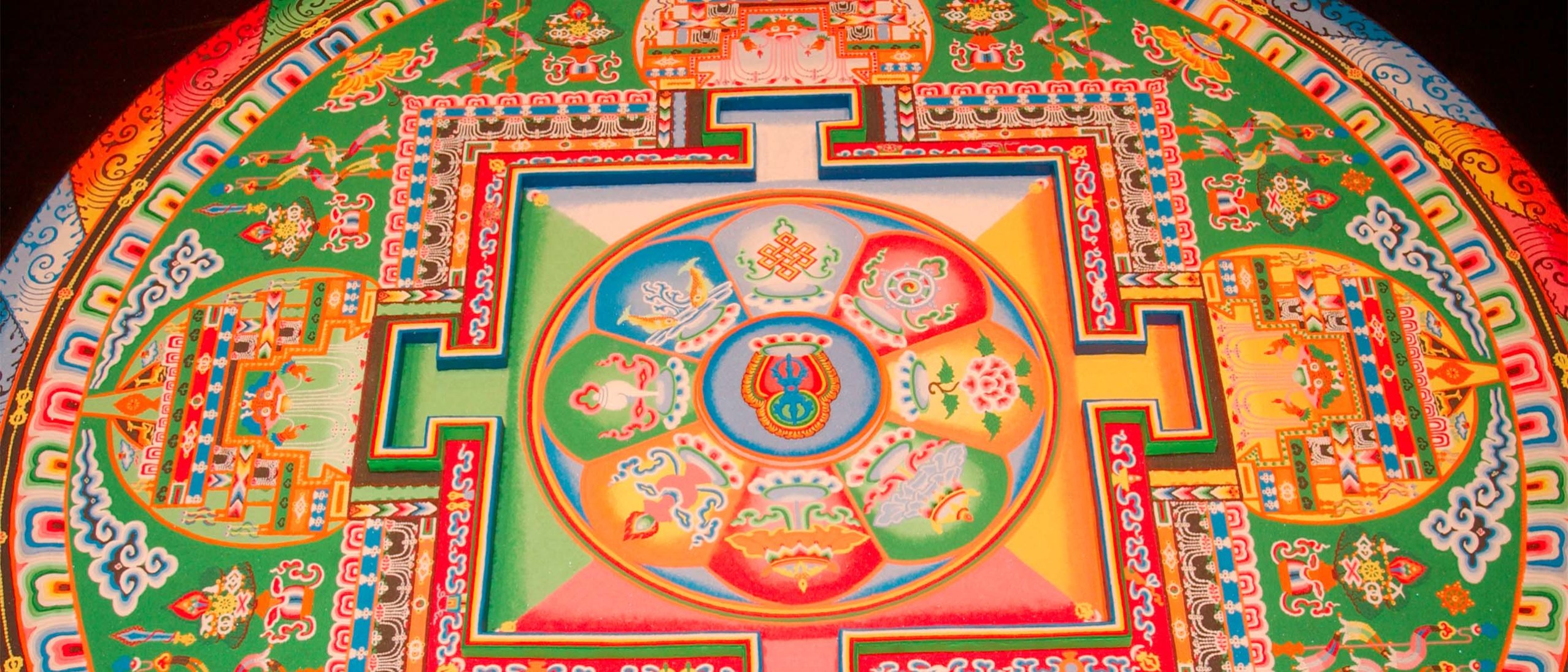 The completed mandala - intricate and colorful - in vivid red, yellow, green, blue, and white.