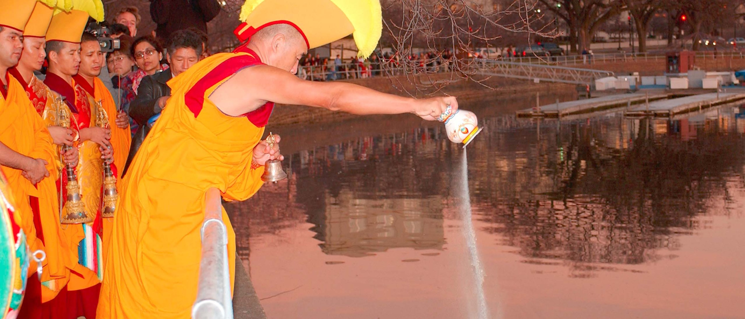 A monk in red and gold robes and a yellow crested headdress pours sand from the mandala into the Tidal Basin. The sun is setting behind the buildings, reflecting a pink and blue sky upon the water.