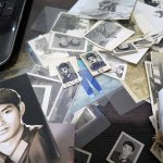 Piles of old family photographs recently sent to Jian in Sydney by his sister who remains in Beijing