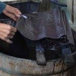 Wu Meitz feeds cloth into the indigo dyebath