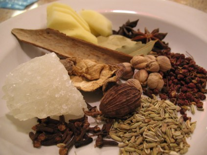Stewing spices used. Clockwise from bottom: fennel seed, cloves, rock sugar, dried tangerine peel, cassia bark, ginger slices, star anise, bay leaves, huajiao, cardamom, and cao guo pod in center