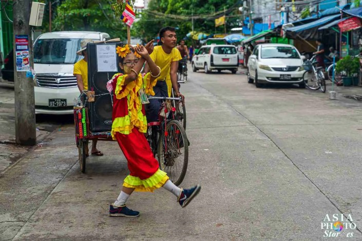 In a neighbor along the Yangon Circle Line, a young girl dances as her brother pedals a cart with muscal accompaniment.