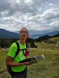 Mężczyzna z mapą spogląda do góry, w tle Pireneje w Andorze