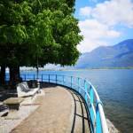 Promenada wzdłuż jeziora, w tle góry i błękitne niebi