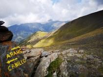 Dwa kierunkowskazy wymalowane żółtą farbą na kamieniu, do Canilli i Arans, w tle Pireneje w Andorze