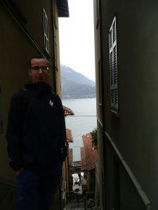 Mężczyzna w ąskiej uliczce w Varennie, w tle jezioro Como