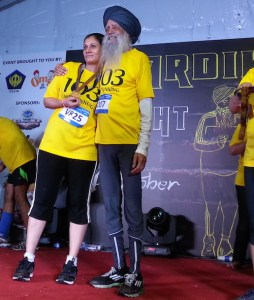Fauja Singh presenting a medal to one of the winners at the Chardi Kala Night Run 2014 in Kuala Lumpur. The runner wore t-shorts bearing 103, his age at the time of the run.