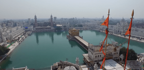 A sevadar adjusting the cloth covering of the nishan sahib outside the Akaal Takht. - SCREEN GRAB FROM ARJIN'S AERIAL SHOOT OF DARBAR SAHIB, AMRITSAR