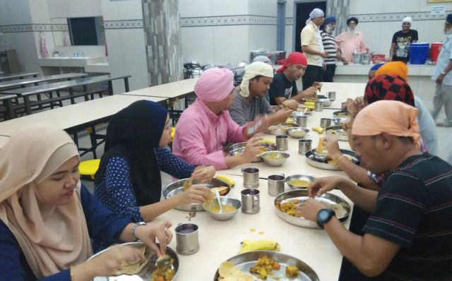 RTM crew berbuka puasa (breaking fast) at Penang gurdwara after their filming session. One team member even got the Sikhs to tie him a turban - PHOTO / DALJIT SINGH