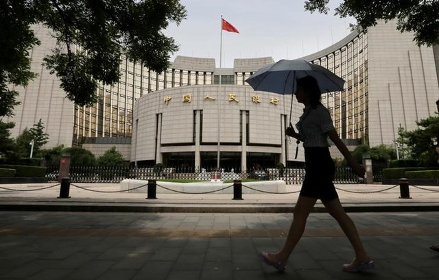 A woman walks past the headquarters of the People's Bank of China (PBOC), the central bank, in Beijing. Photo: Reuters/Jason Lee