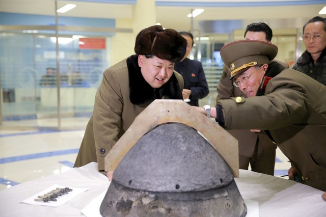 North Korean leader Kim Jong-un looks at a rocket warhead tip after a simulated test of atmospheric re-entry of a ballistic missile, at an unidentified location in this undated image. Photo: KCNA via Reuters