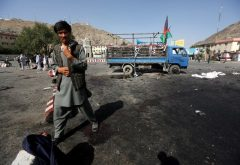 An Afghan man walks at the site of a suicide attack in Kabul