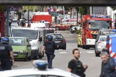 Police and rescue workers stand at the scene after two assailants had taken five people hostage in the church at Saint-Etienne-du -Rouvray near Rouen in Normandy