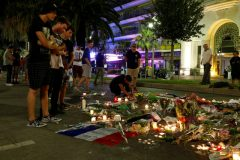 People react near flowers placed on the road in tribute to victims, three days after an attack by the driver of a heavy truck who ran into a crowd on Bastille Day killing scores and injuring as many on the Promenade des Anglais, in Nice