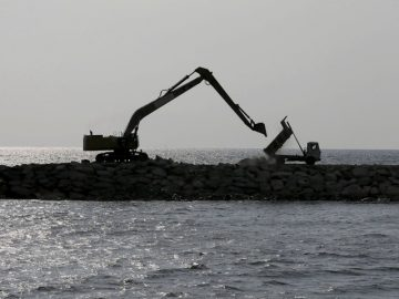 """A tipper truck unloads rocks as part of a process to reclaim the sea front next to an excavator at """"Colombo Port City"""" construction site, backed by Chinese investment, is seen in Sri Lanka"""
