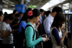 A woman looks at her mobile phone while waiting inside a train station in Bangkok