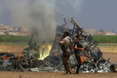 Men inspect the wreckage of a Russian helicopter that had been shot down in the north of Syria's rebel-held Idlib province