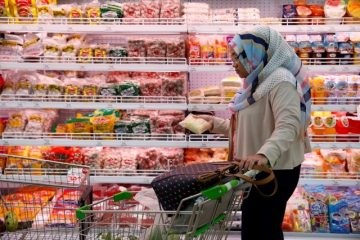 A woman holds a package of food during shopping at a Foodmart Fresh supermarket in Jakarta, Indonesia June 8, 2016. Photo: Reuters/Beawiharta