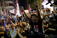 Supporters of the Hong Kong badminton team react as they watch the live broadcast of the Rio Olympics mixed doubles badminton match between Hong Kong and China at Mongkok shopping district in Hong Kong
