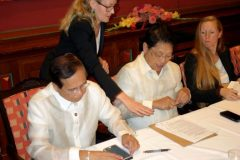 Philippine government negotiators Jesus Dureza and Silvestre Bello sign an indefinite ceasefire agreement with communist rebels at a meeting in Oslo