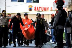 Police remove the body of a suicide bomber from the scene of an attack in Solo, Central Java, Indonesia