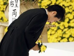 Japan's Prime Minister Shinzo Abe bows as he offers a chrysanthemum flower to the war dead during a memorial service ceremony marking the anniversary of Japan's surrender in World War Two at Budokan Hall in Tokyo
