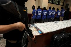 Police present suspects and packets of methamphetamine as evidence following an illegal narcotics raid at police headquarters in Jakarta