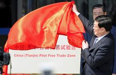 "Tianjin municipal Mayor Huang Xingguo removes the veil covering a sign reading ""China (Tianjin) Pilot Free Trade Zone"", at an unveiling ceremony in Tianjin municipality"