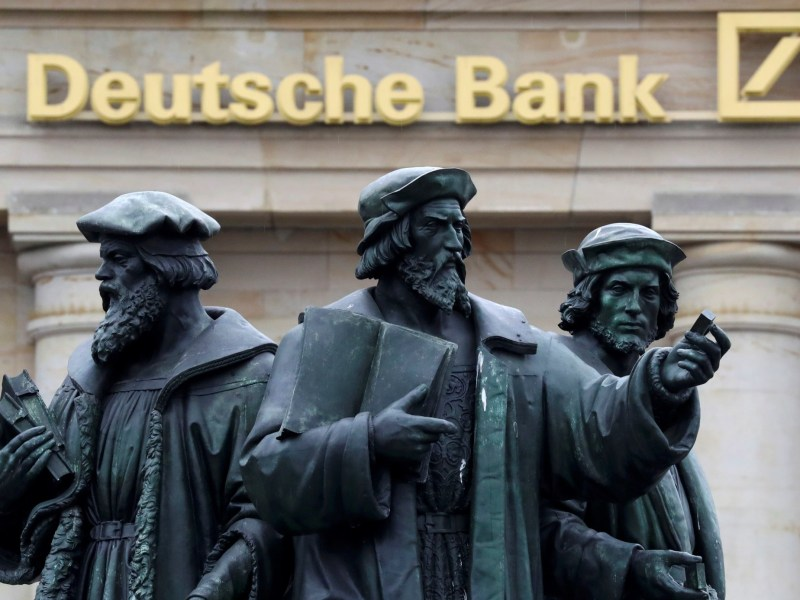 A statue is pictured next to the logo of Germany's Deutsche Bank in Frankfurt, Germany. Photo: Reuters/Kai Pfaffenbach