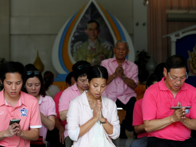Well-wishers wear pink shirts as they pray in front of a picture of Thailand's King Bhumibol Adulyadej at Siriraj Hospital in Bangkok, Thailand, October 11, 2016. REUTERS, Chaiwat Subprasom