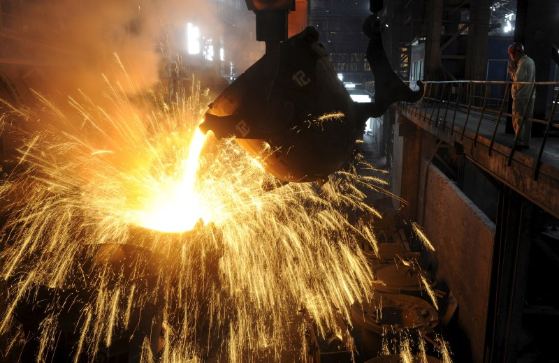 An employee monitors molten iron being poured into a container at a steel plant in Hefei, Anhui Province. Photo: Reuters