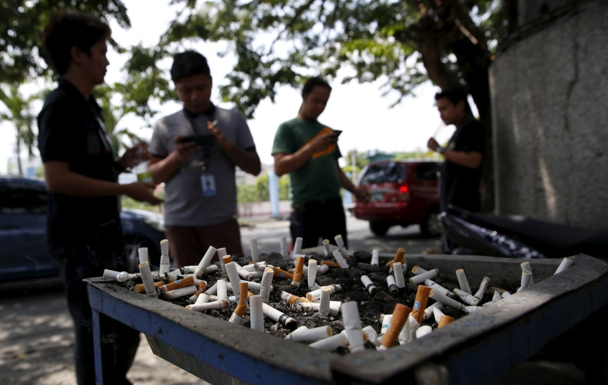 Men smoke cigarettes near a tray filled with stubs beside a road in Manila. Photo: Reuters/Erik De Castro