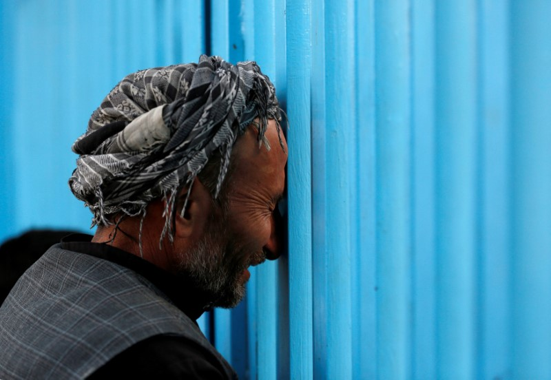 An Afghan mourns at the gate of the Sakhi Shrine after an overnight attack in Kabul, Afghanistan October 12, 2016. REUTERS/Mohammad Ismail