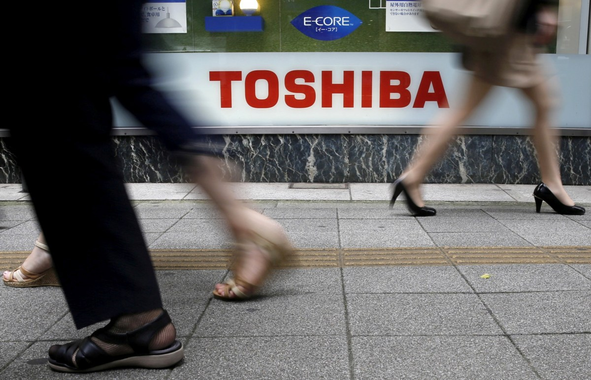 Pedestrians walk past a logo of Toshiba Corp outside an electronics retailer in Tokyo, Japan. Reuters