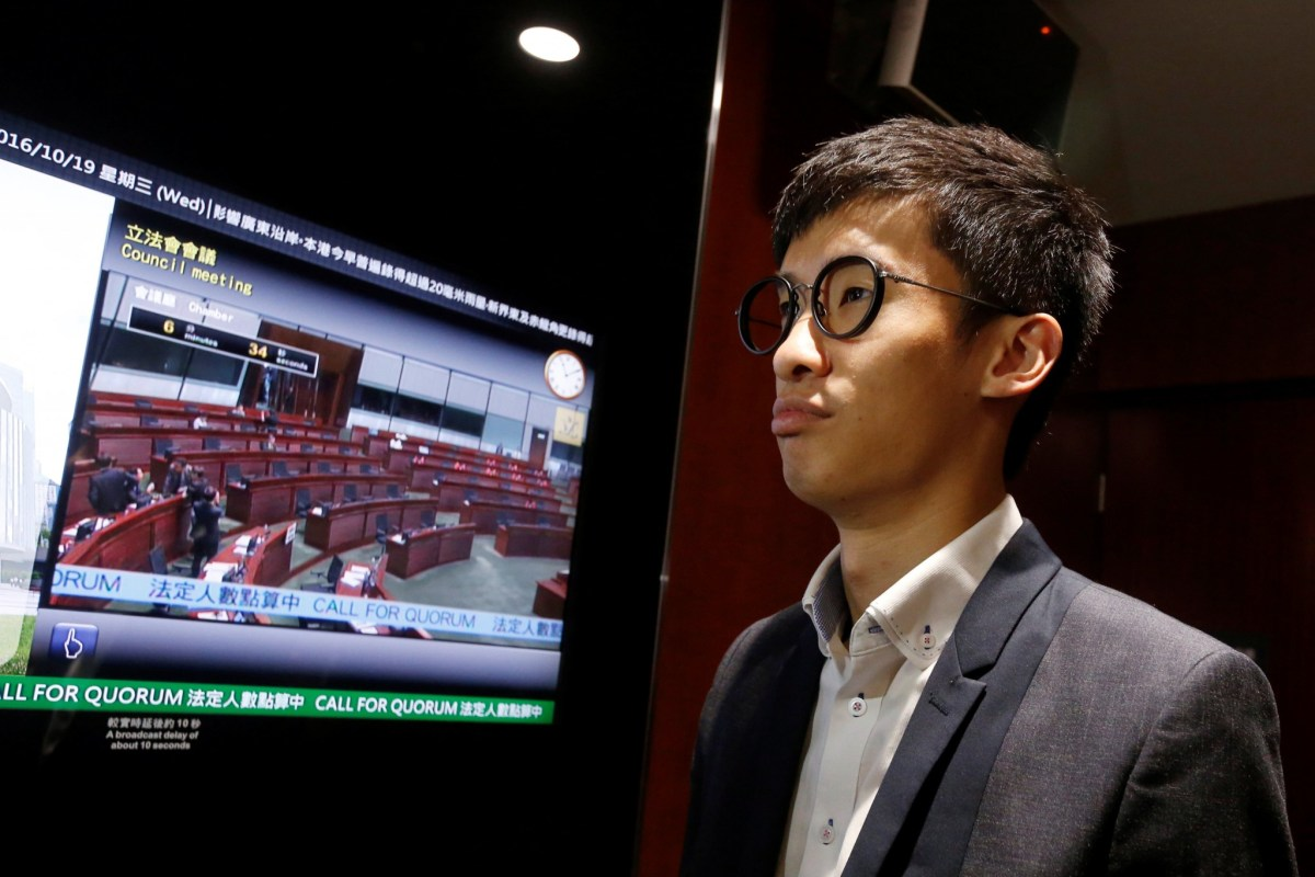 Activist Baggio Leung stands beside a monitor showing a nearly empty chamber after pro-Beijing lawmakers staged a walk-out to stall his swearing-in at the Legislative Council in Hong Kong.  Photo: REUTERS/Bobby Yip