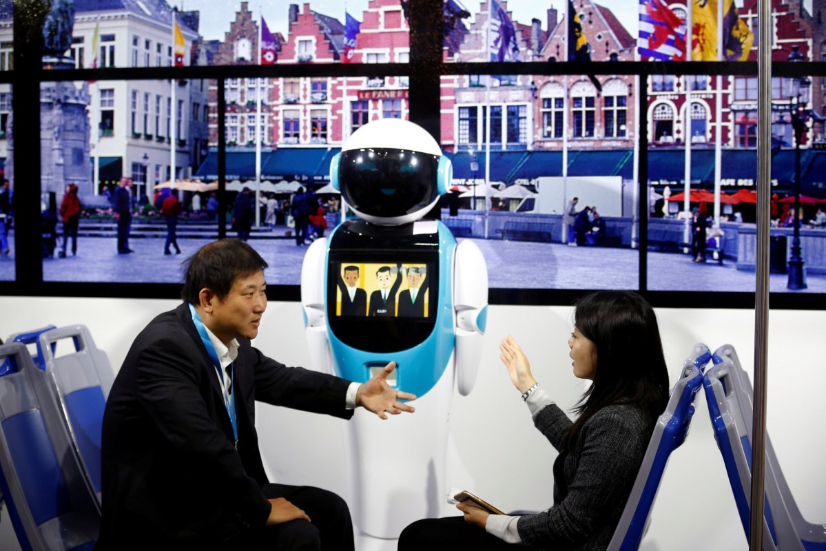 Is he with you? Visitors chat as they sit in a public transport simulator at the World Robot Conference 2016 in Beijing, China. The conference runs from October 21 to 25. Photo: Reuters/Thomas Peter