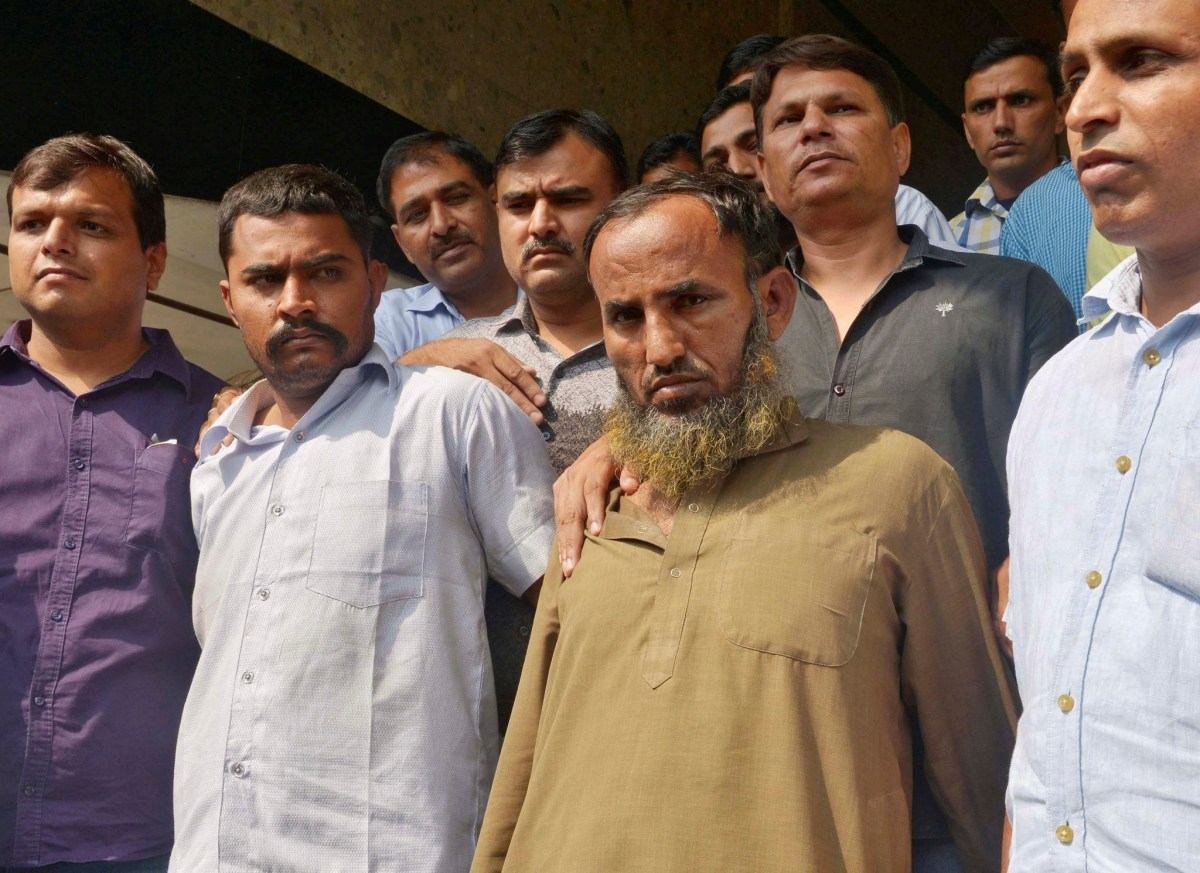 Plain-clothes policemen present two Indian men who are accused of spying for Pakistan, in New Delhi. Photo: Reuters