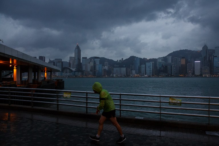 A man jogs along a promenade running along Victoria Harbour as Typhoon Haima approaches Hong Kong early on October 21, 2016, shortly after the typhoon signal eight warning was raised. Typhoon Haima approached Hong Kong on October 21 after killing at least four in the Philippines. / AFP PHOTO / Anthony WALLACE
