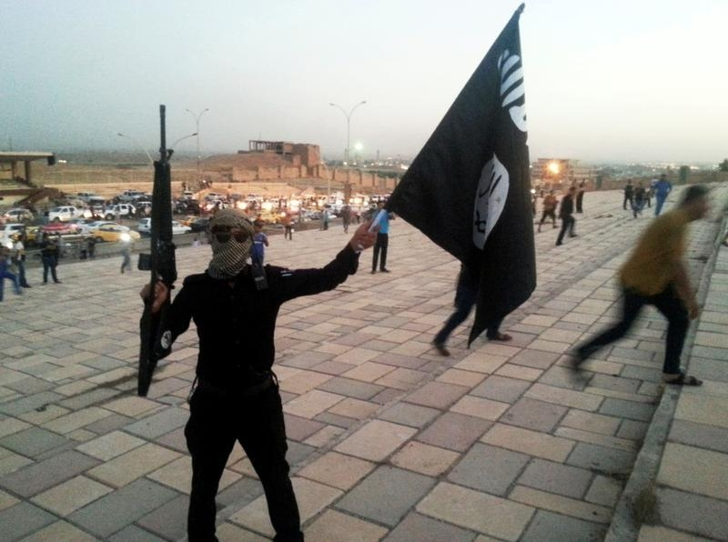 An Islamic State fighter holds an IS flag on a street in the city of Mosul, on June 23, 2014. Photo: Reuters / Stringer