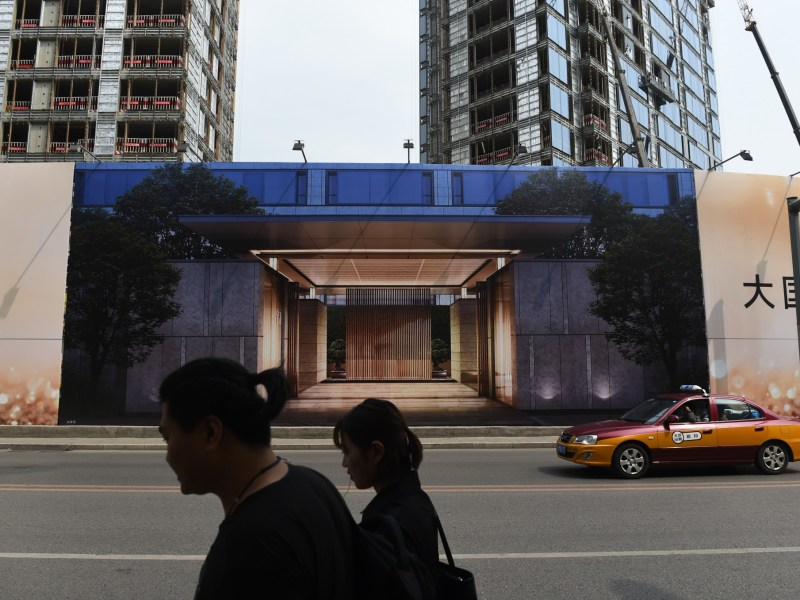 People walk past a billboard advertising a new housing complex outside a construction site in Beijing. Photo: GREG BAKER / AFP
